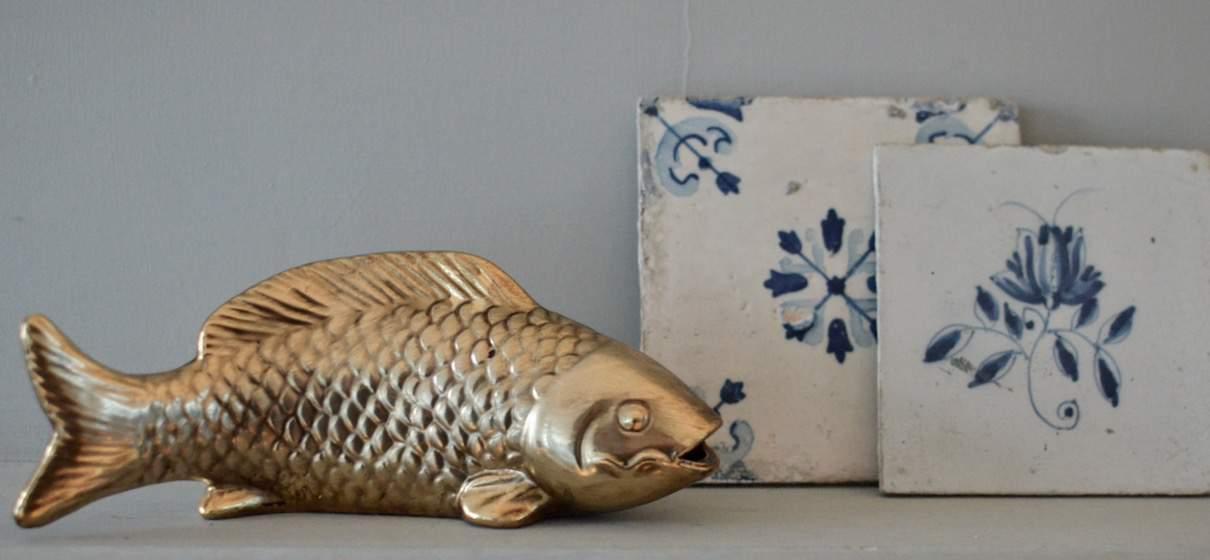Deze decoratie vis is uitgevoerd in een gouden klaar. De vis kan neergezet en opgehangen worden.