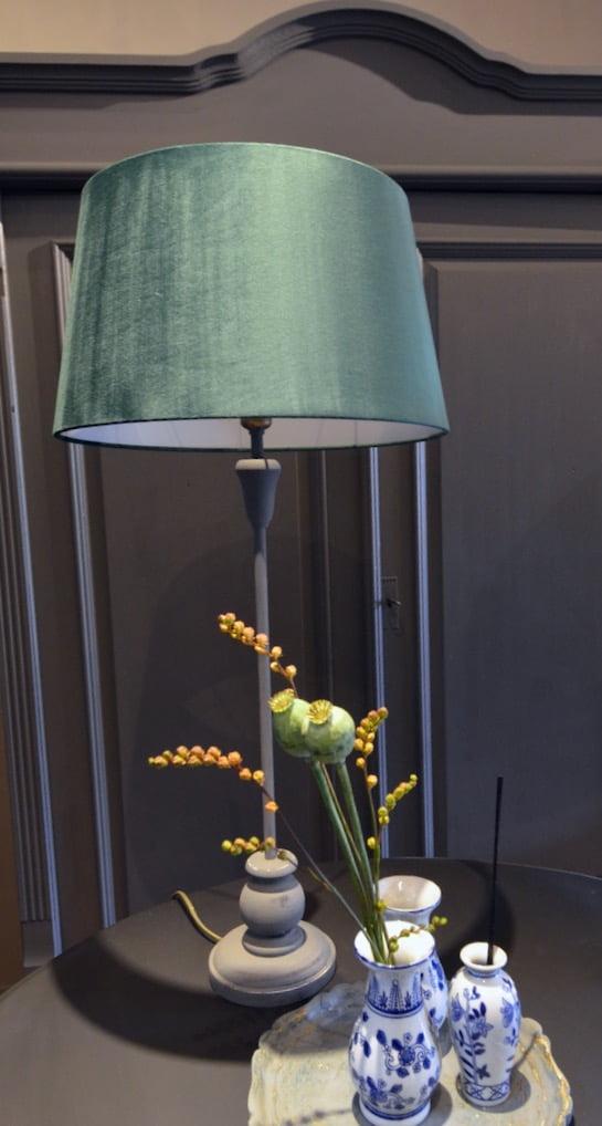 Hoge tafellamp met grijze brocante stijl poot en groene kap. Als je subtiel wat kleur wilt toevoegen, dan kan deze lamp daar nog wel eens voor zorgen. Compleet met kap.